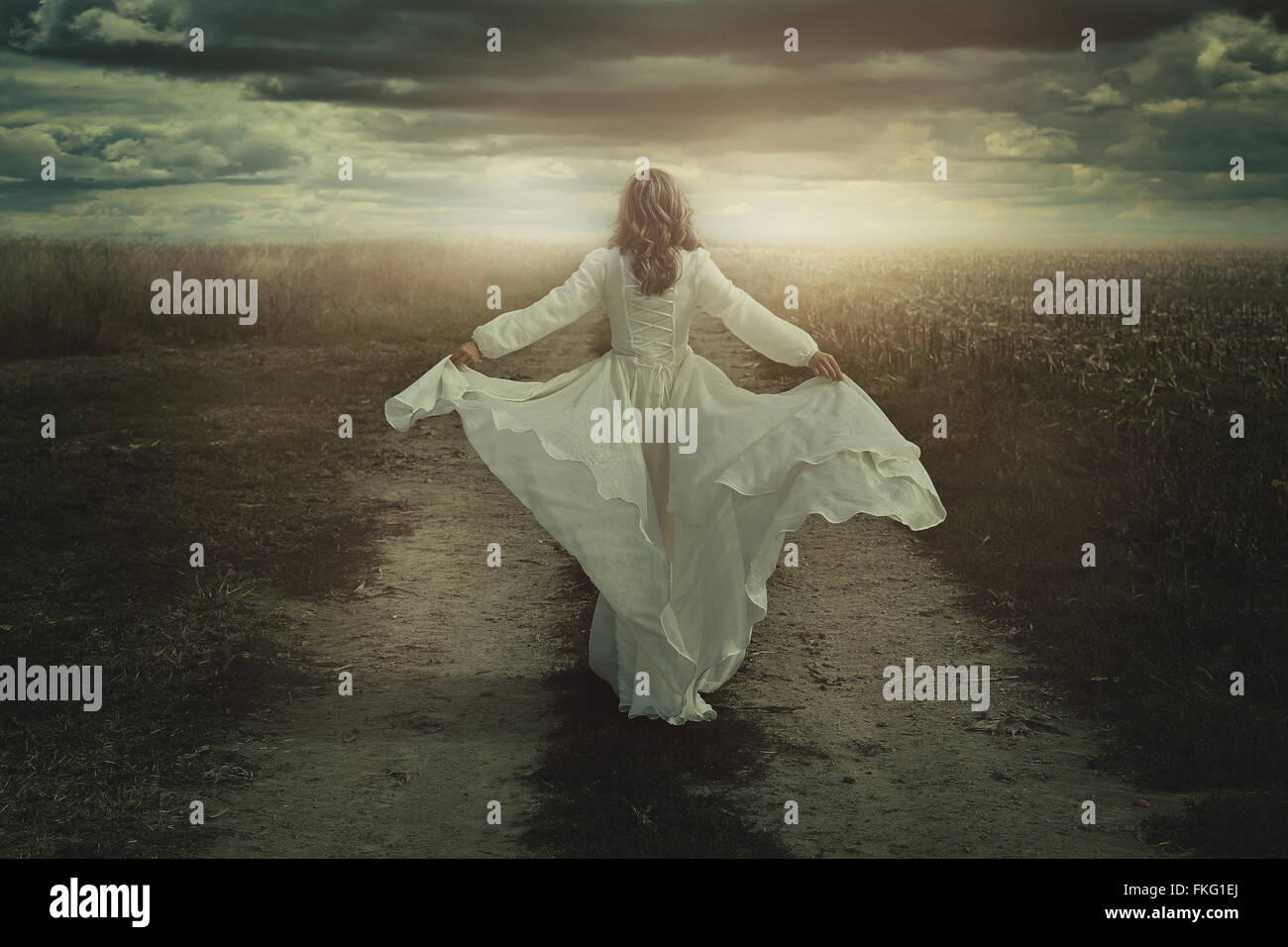 Woman running free in a desolate dark land. Surreal manipulation - Stock Image