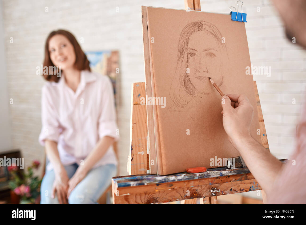 Male artist drawing portrait of woman - Stock Image