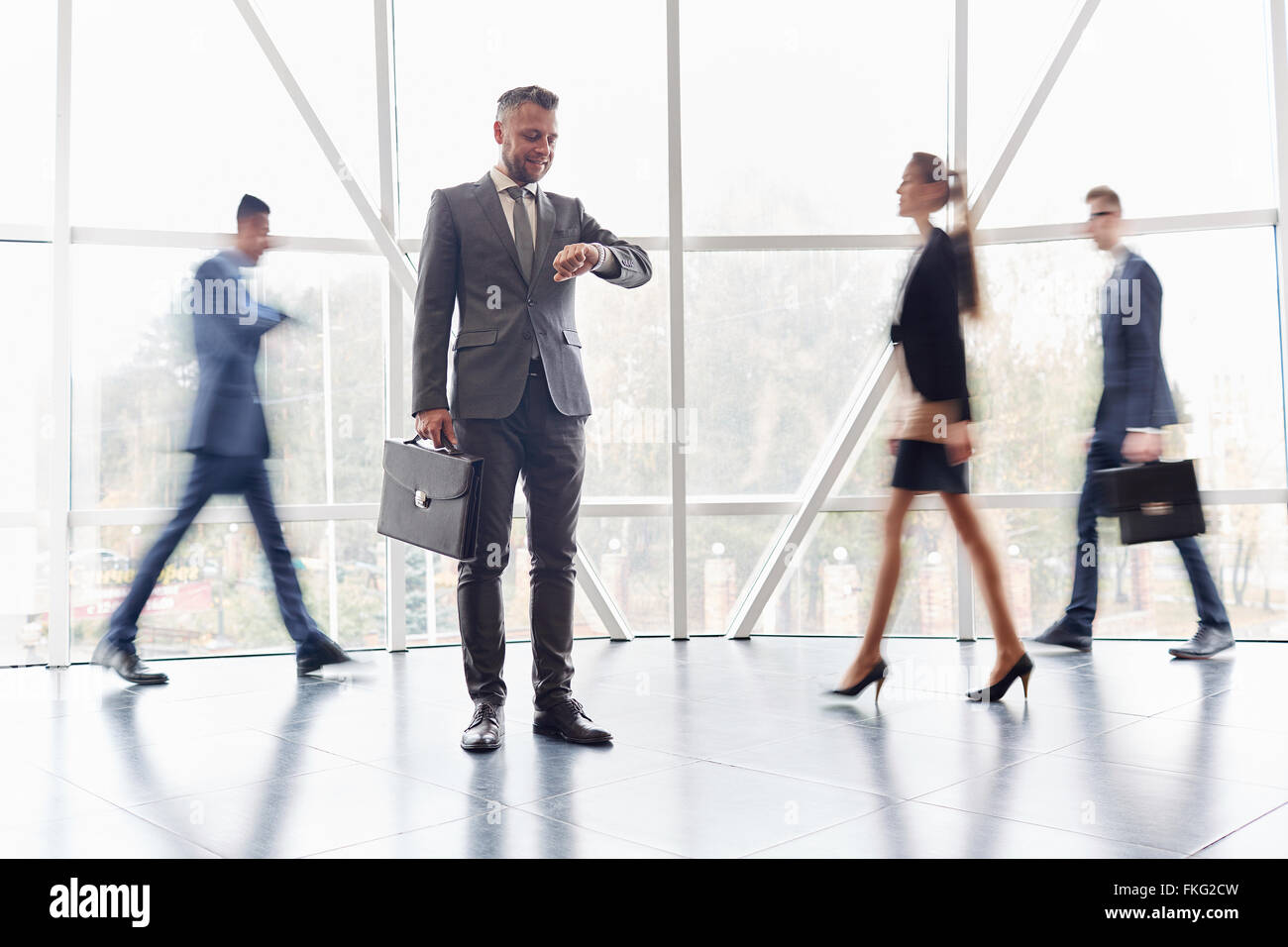 Businessman with suitcase looking at his watch among business people going behind him - Stock Image