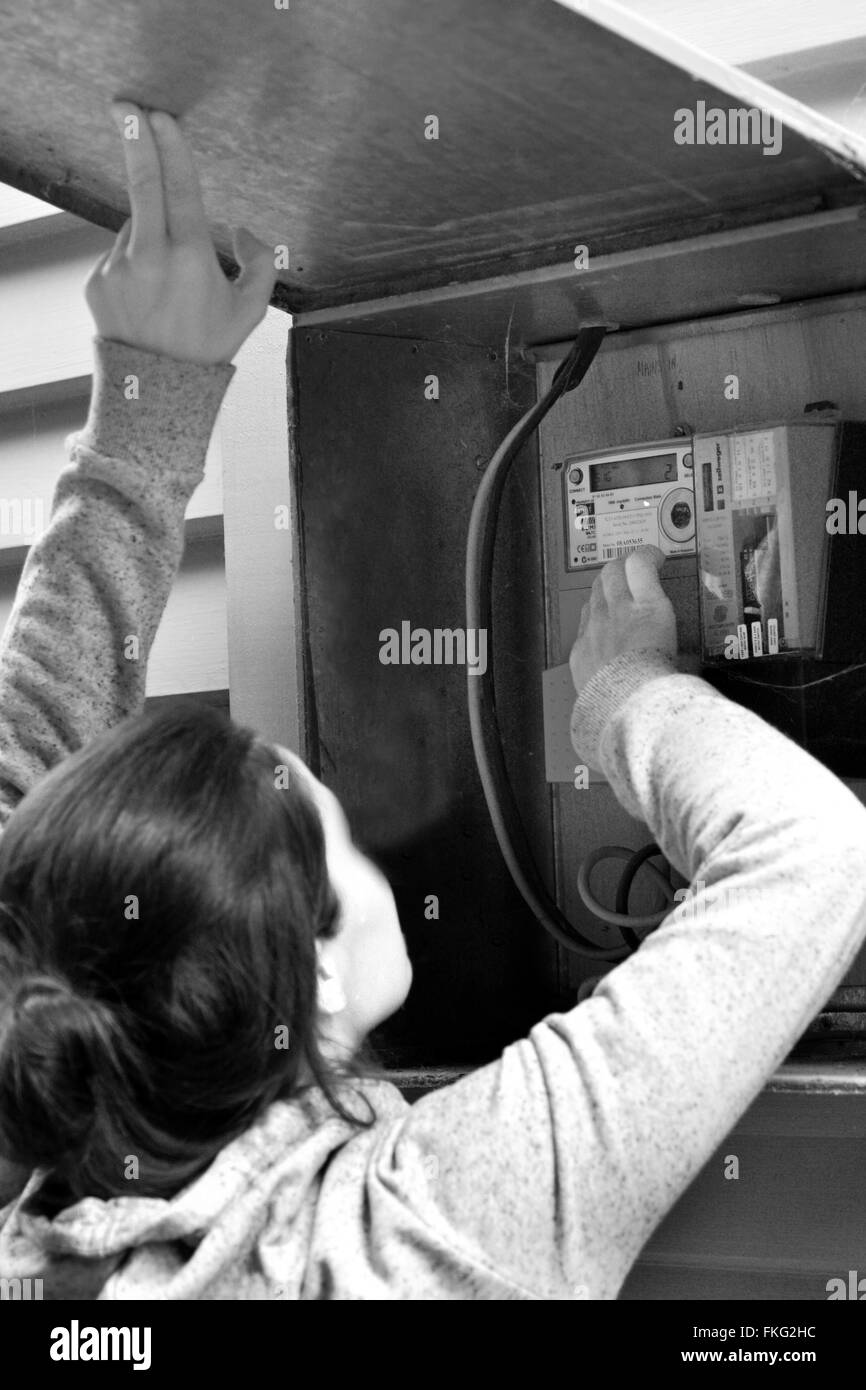 AUCKLAND - DEC 06 2015:Woman check her smart meter.The safety of smart meters raised concerns, mainly because they - Stock Image