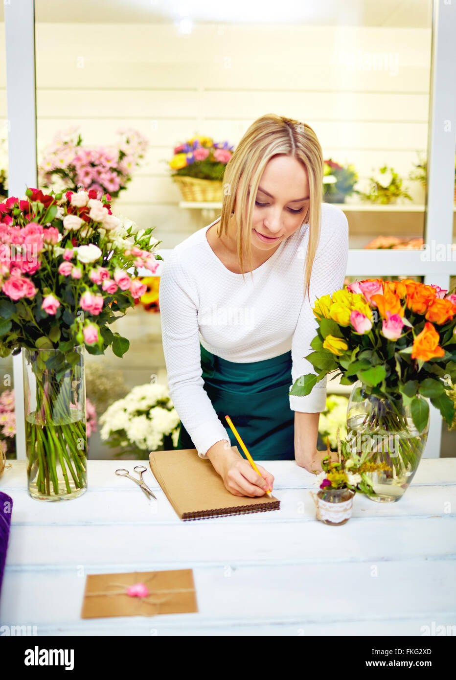 Beautiful young female florist writing something at notebook while standing at her working place - Stock Image
