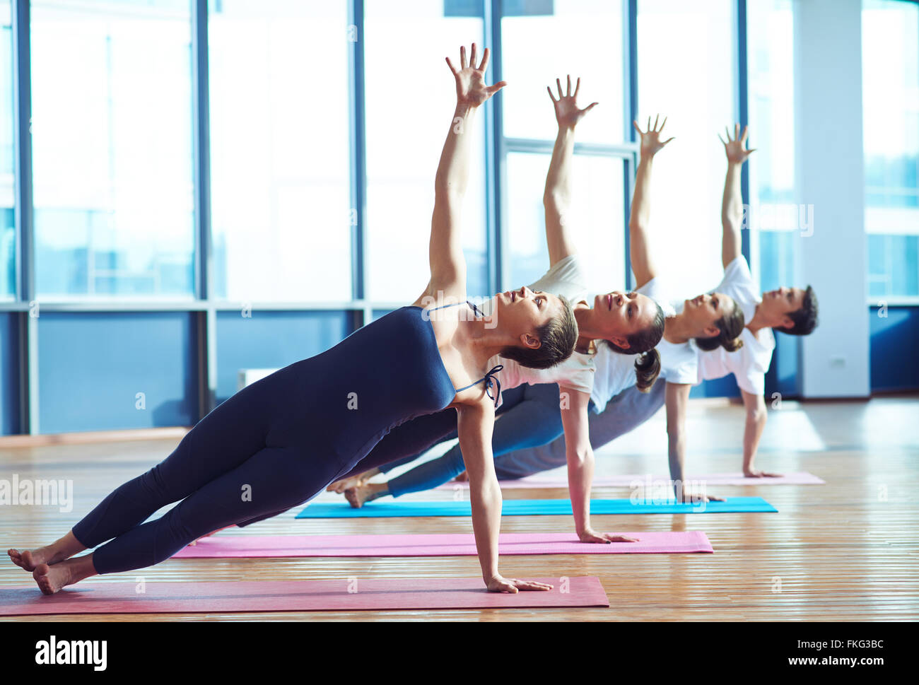 Group of young people practicing side plank yoga pose during a class in gym - Stock Image