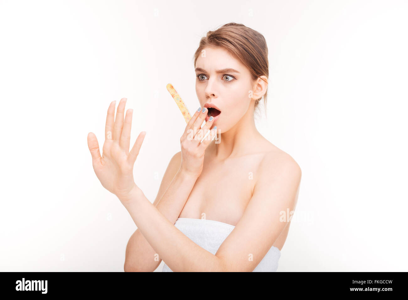 Beauty portrait of shocked young woman with emery board looking at her nails over white background - Stock Image