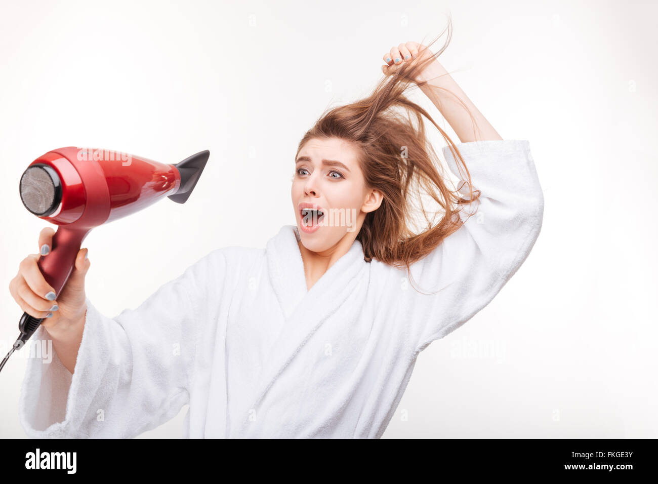 Funny frightened young woman in bathrobe  drying her hair and scared of dryer over white background - Stock Image