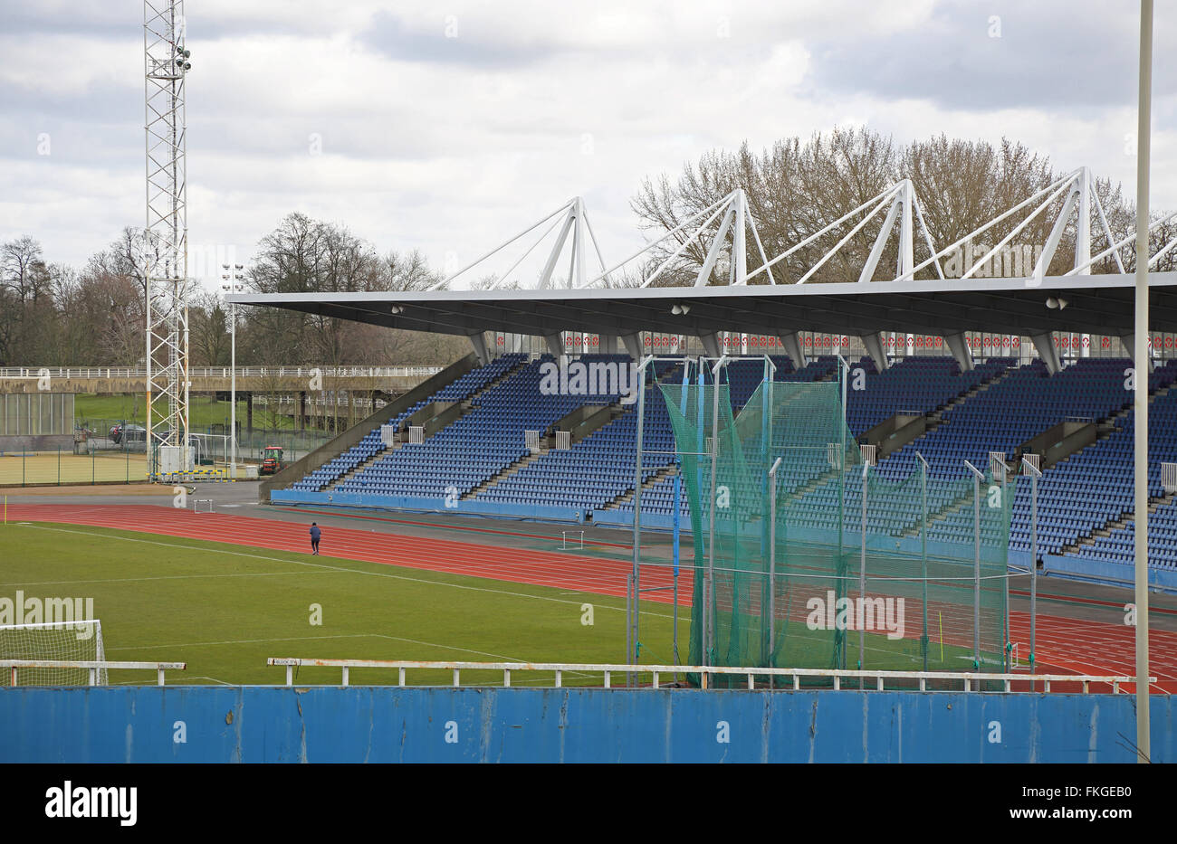 A lone,elderly runner practices on the athletics track in front of an empty grandstand at Crystal Palace Stadium. - Stock Image