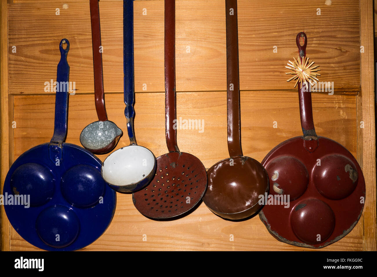 Ladles and pans on a kitchen wall - Stock Image