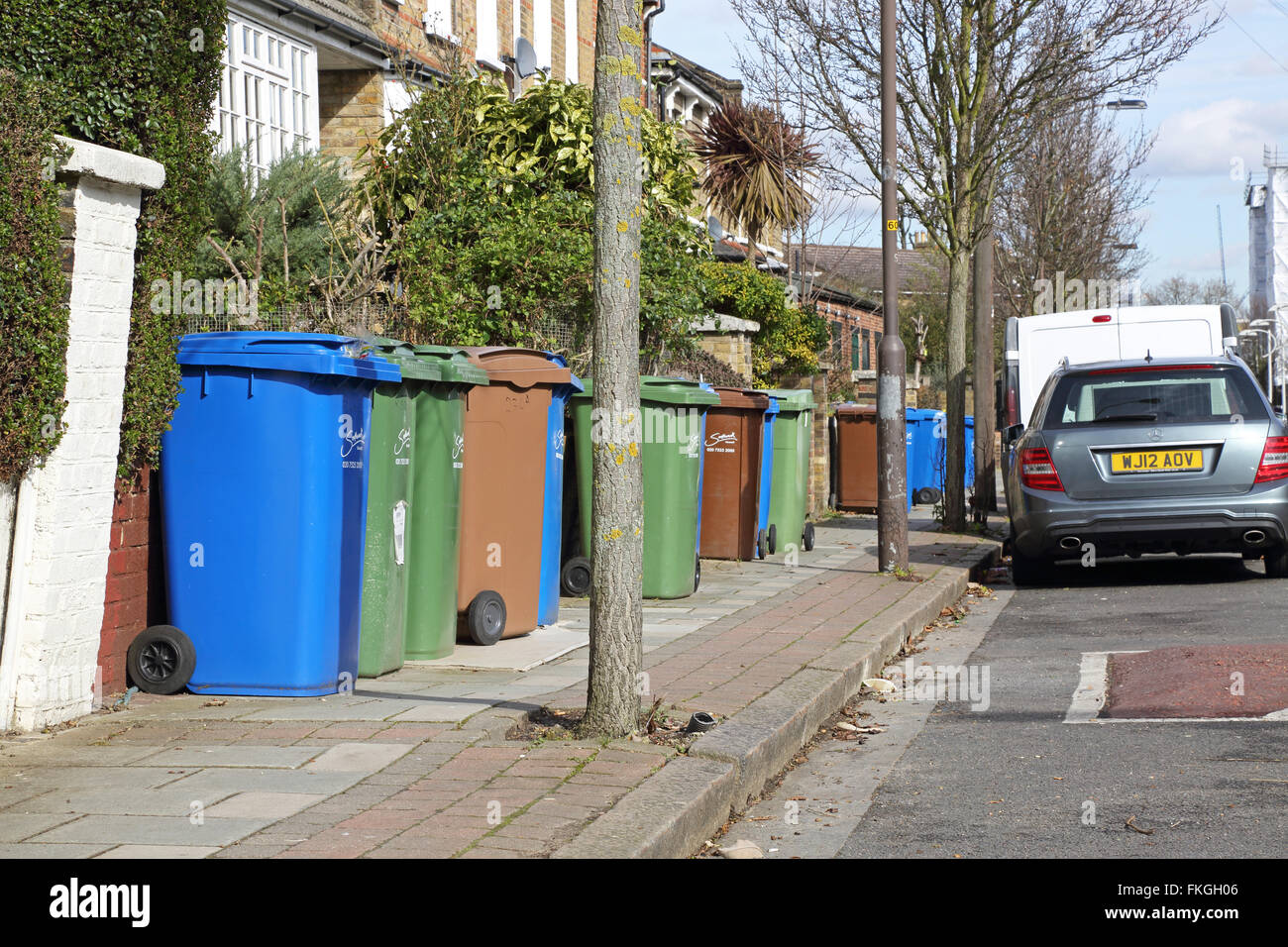 Household refuse recycling bins take up most of the pavement space on a South London street in Southwark Stock Photo