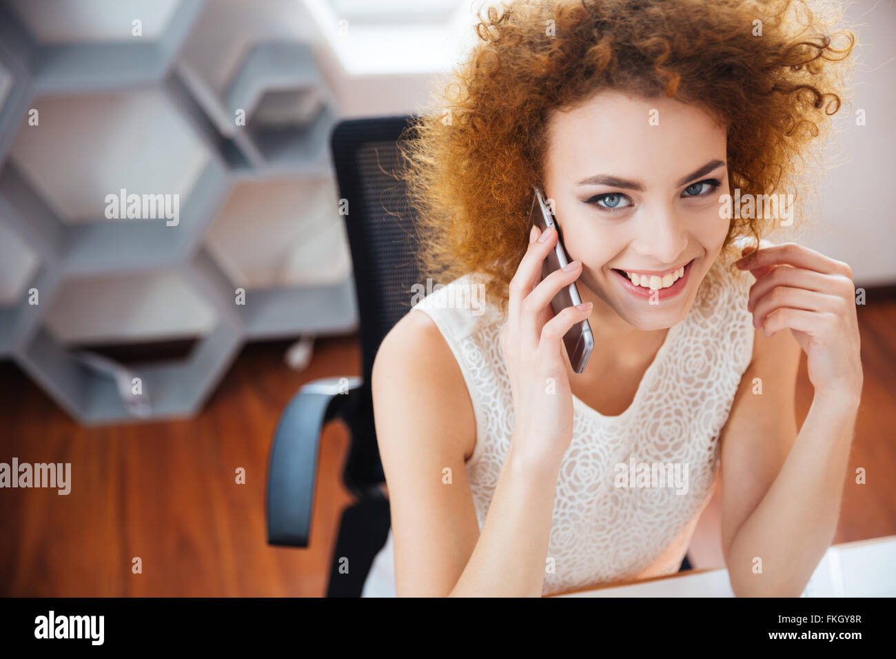 Smiling beautiful business woman with curly red hair talking on mobile phone on workplace in the office - Stock Image