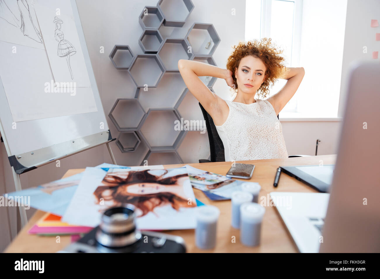 Relaxed pensive curly young woman photographer sitting on workplace with hands behind head - Stock Image