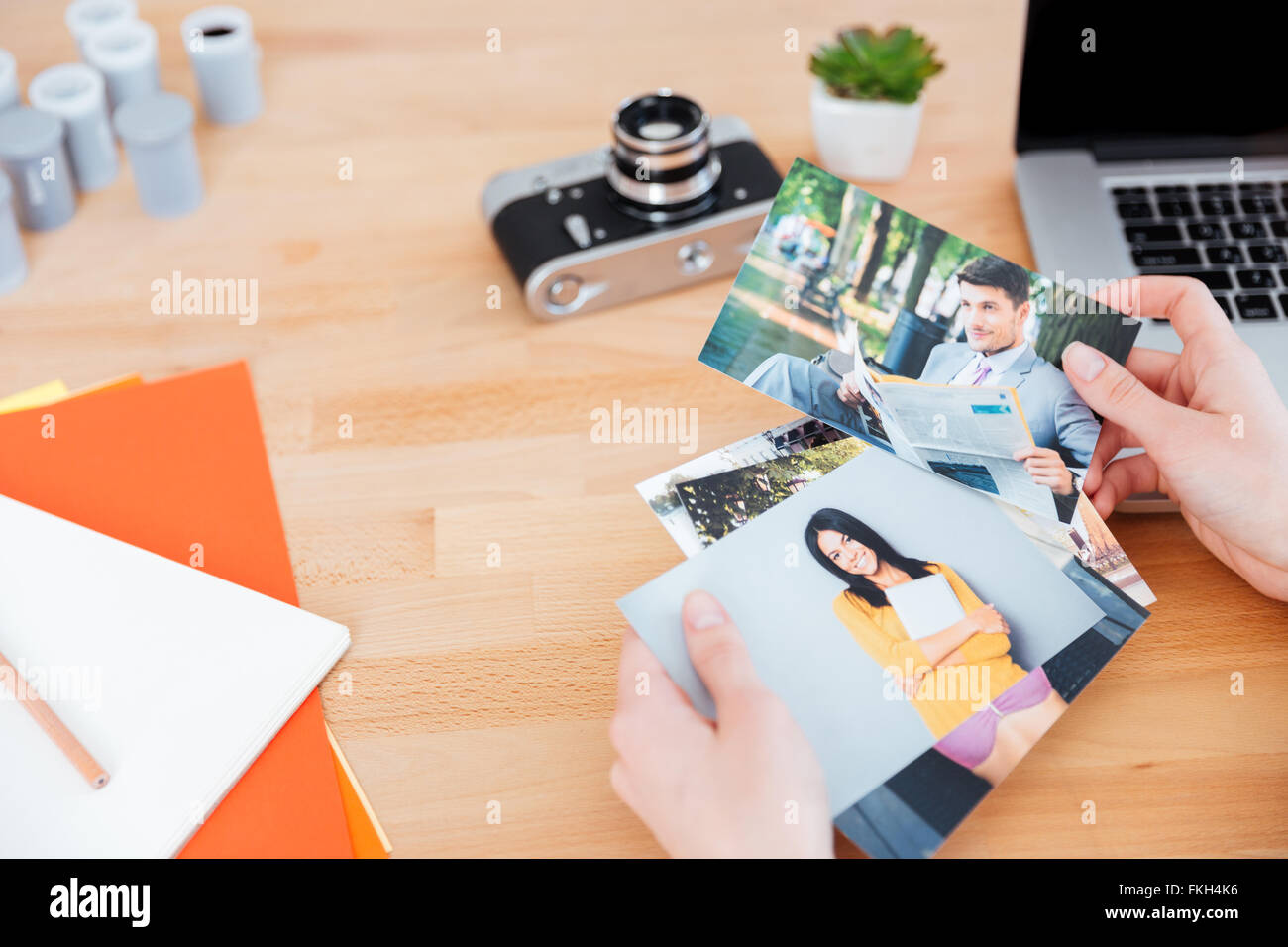 Top view of photos of models holded by young woman photographer at the table Stock Photo