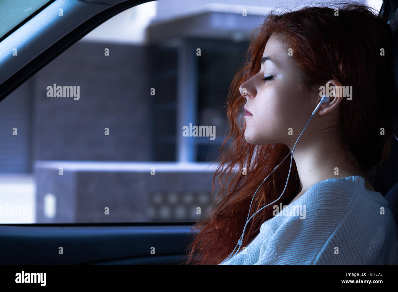 Woman with Earbuds Listening to Music in a Car - Stock Image