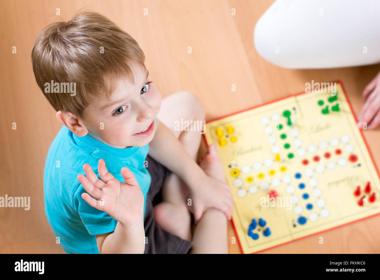 Child playing in board game sitting on floor Stock Photo