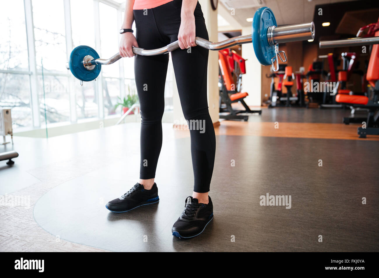 Closeup of legs of young woman athlete standing and exercising with barbell in gym - Stock Image