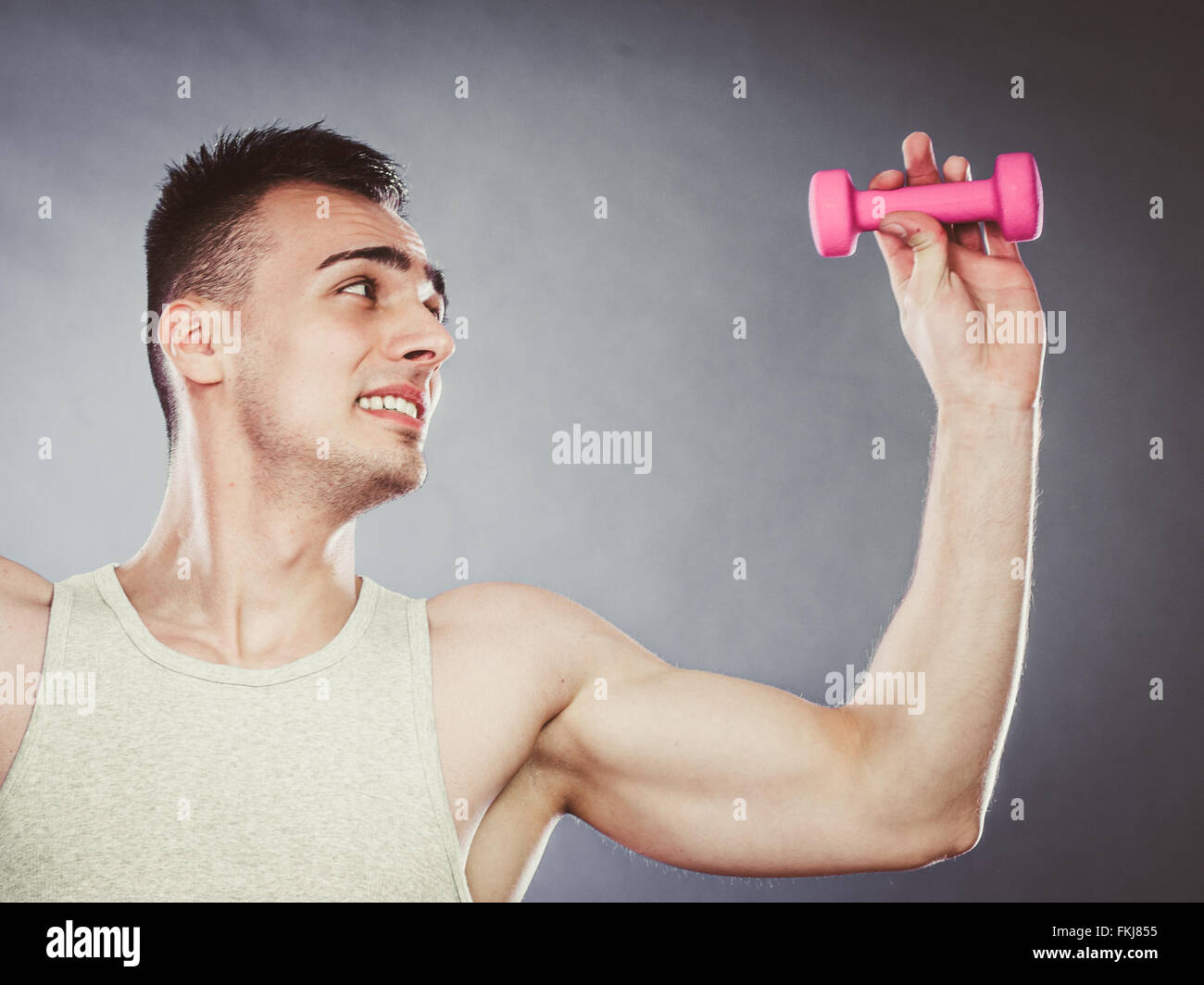 Funny sporty fit man lifting light dumbbell weight. Young muscular ...