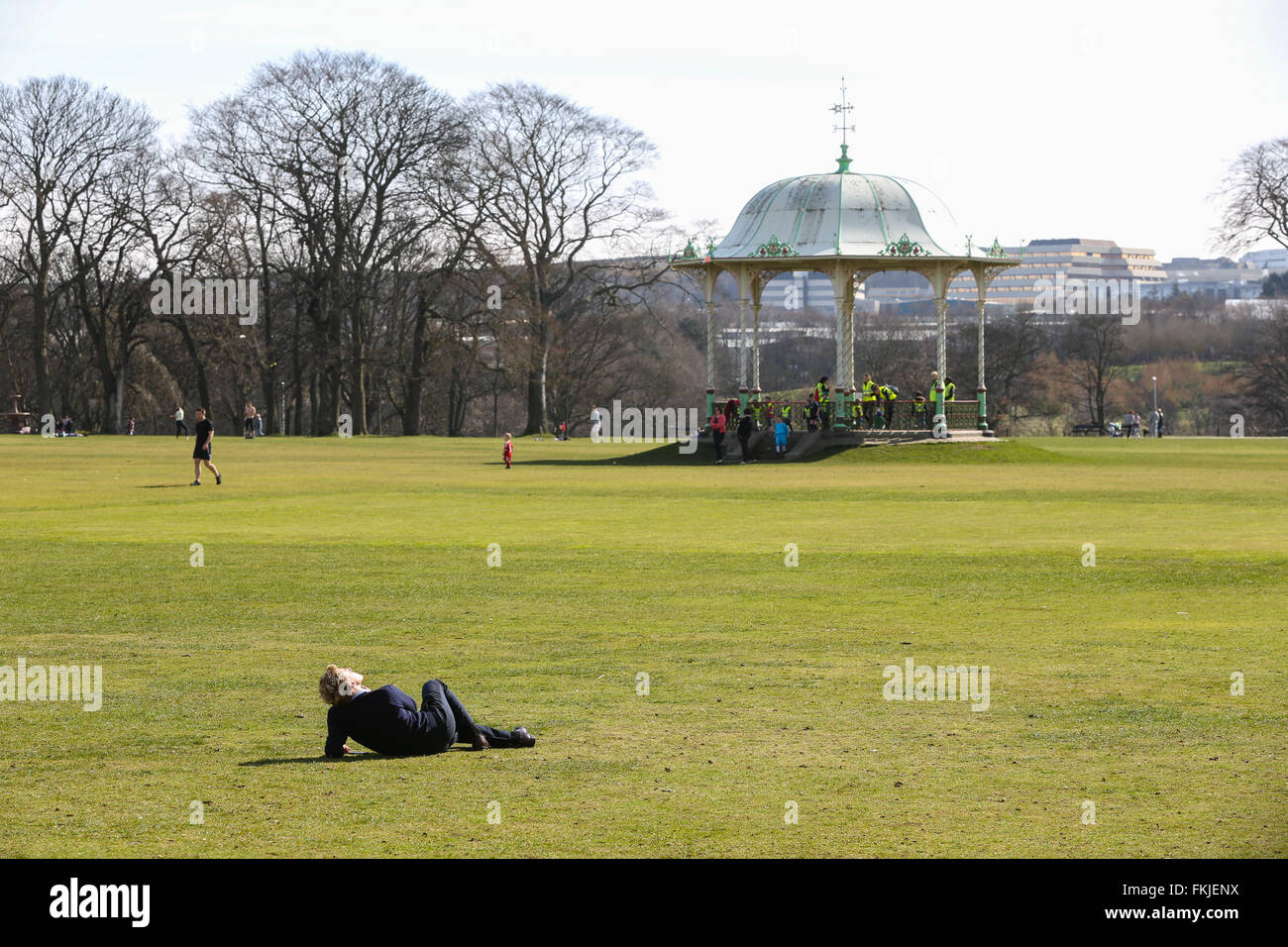 People enjoying the sun in Duthie Park, Aberdeen, Scotland, UK, with the bandstand in the background - Stock Image