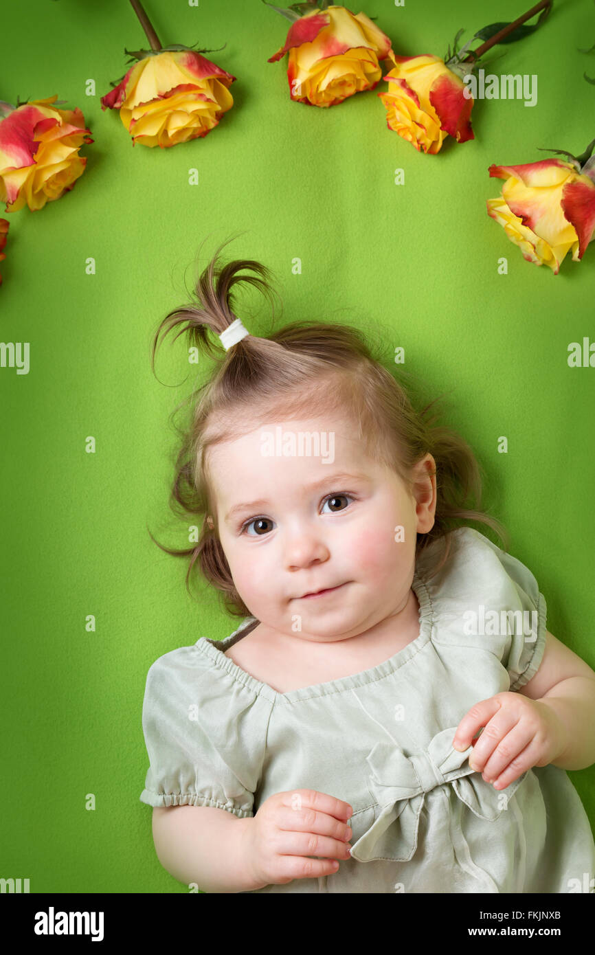 pretty little girl lying on green blanket with yellow roses - Stock Image
