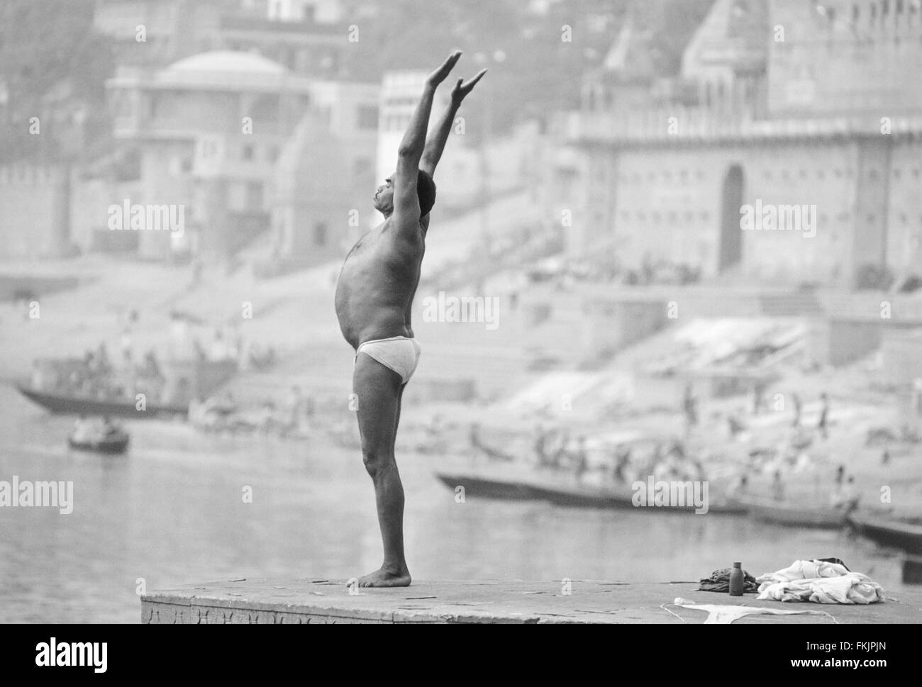 At sunrise guy doing yoga postures,poses,routine facing rising sun.On bathing ghat above sacred River Ganges, Varanasi,India. - Stock Image