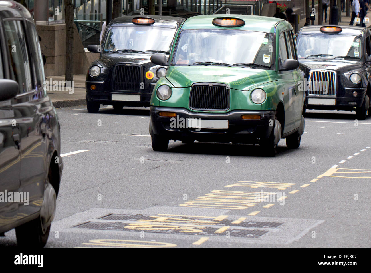 Four iconic, famous London black cab taxis travelling through Canary Wharf Stock Photo
