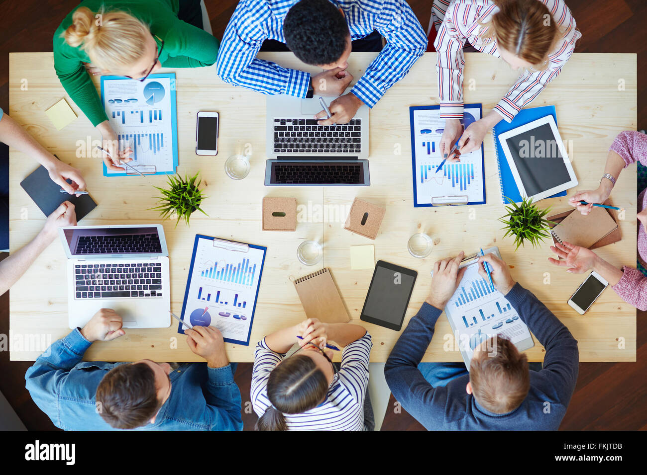 Above view of business team sitting around table and working - Stock Image