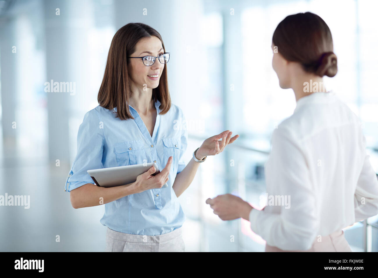 Young woman with touchpad explaining something to her partner - Stock Image