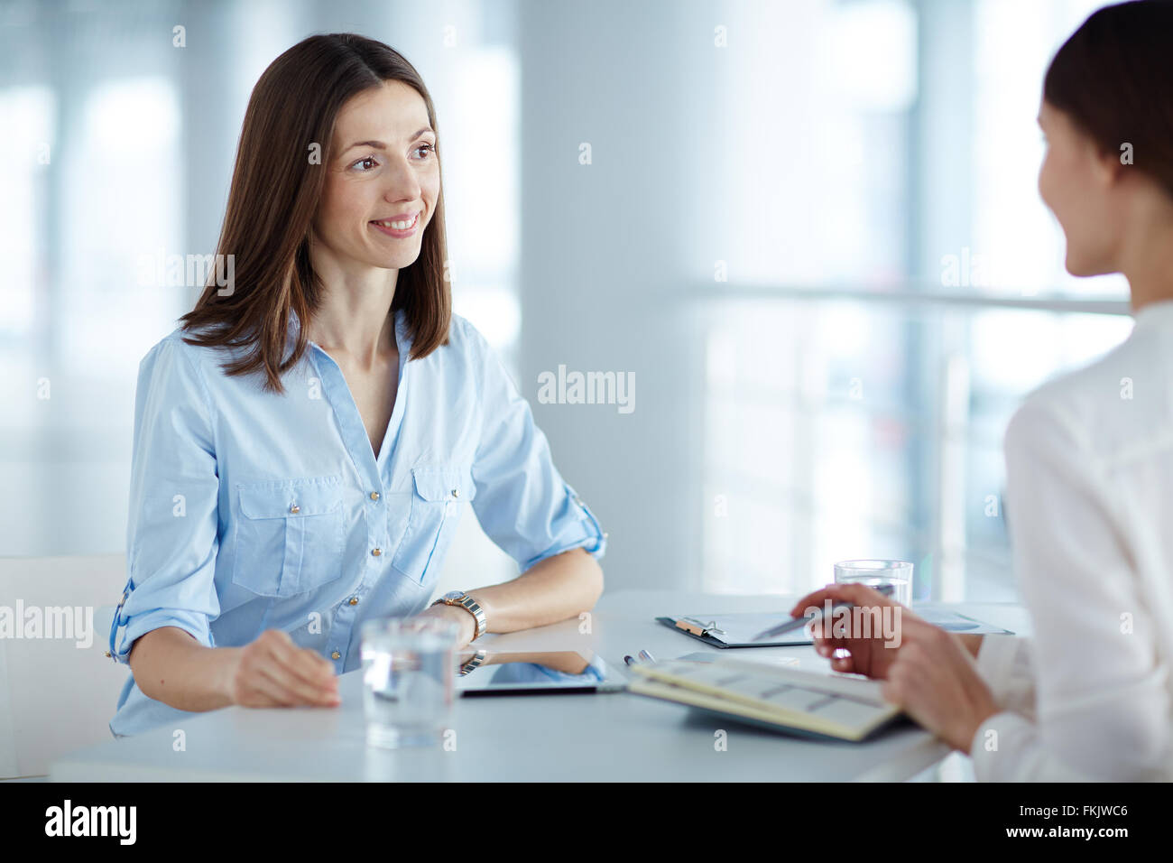 Smiling young woman having a business interview - Stock Image