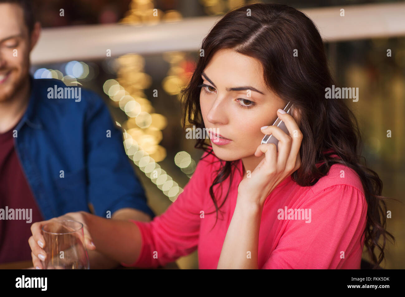 woman with smartphone and friends at restaurant - Stock Image