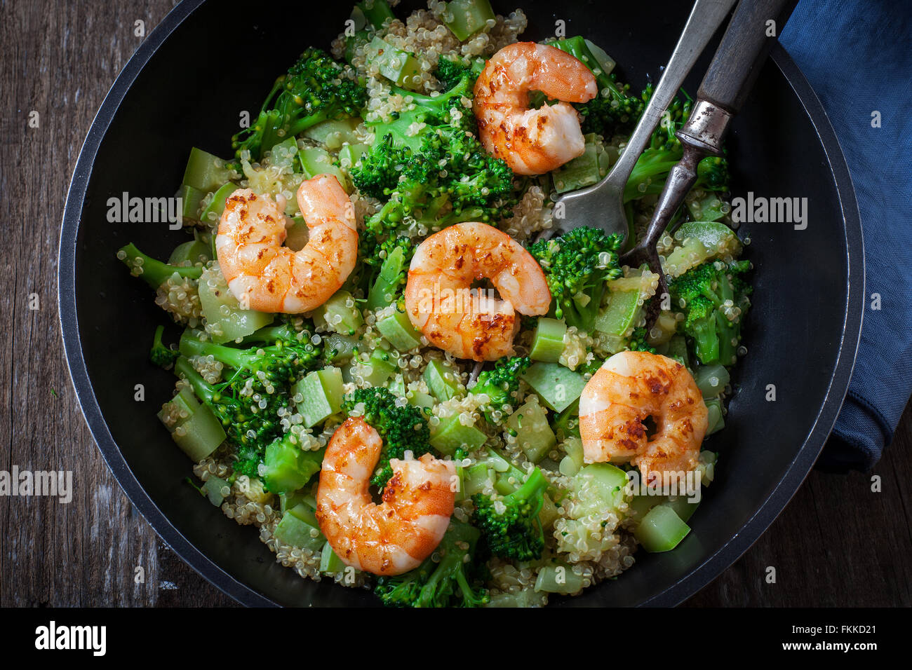 roasted garlic broccoli quinoa salad with prawns on pan - Stock Image