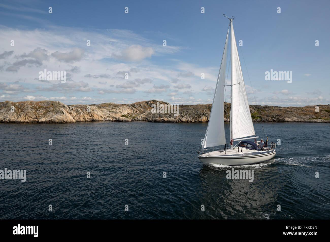 Yacht sailing along rocky coastline, Bohuslän Coast, Southwest Sweden, Sweden, Scandinavia, Europe - Stock Image