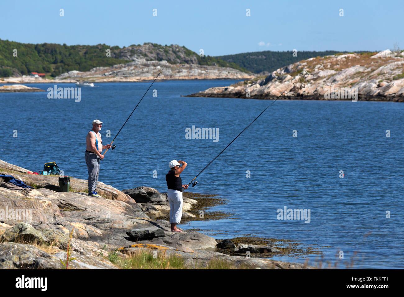 Fishing from rocky coastline, near Marstrand, Southwest Sweden, Sweden, Scandinavia, Europe - Stock Image