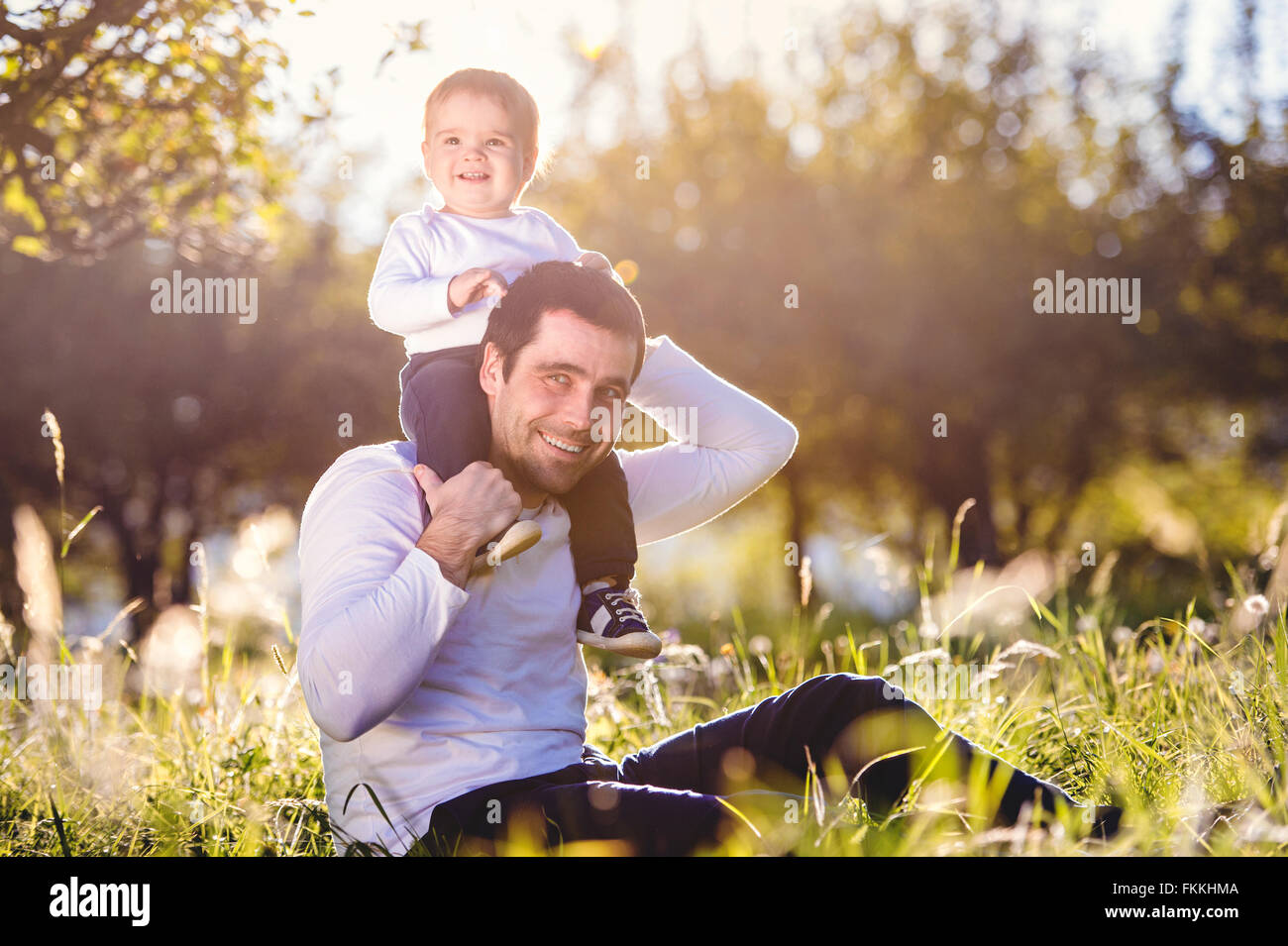 Father carrying son on shoulders, sitting on the grass - Stock Image