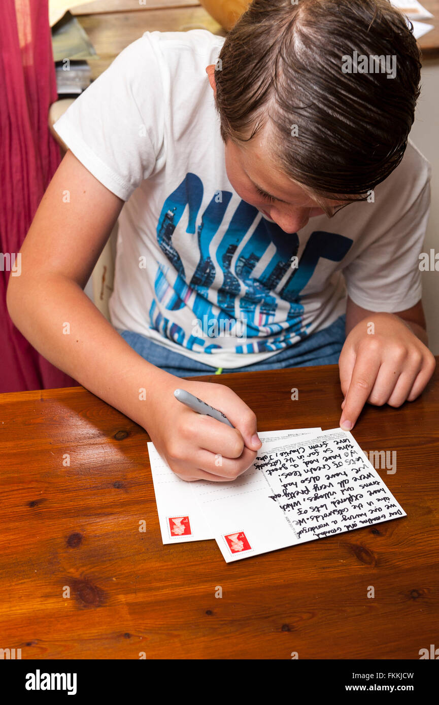 An 11 year old boy writes a postcard from his family holiday in the Uk - Stock Image