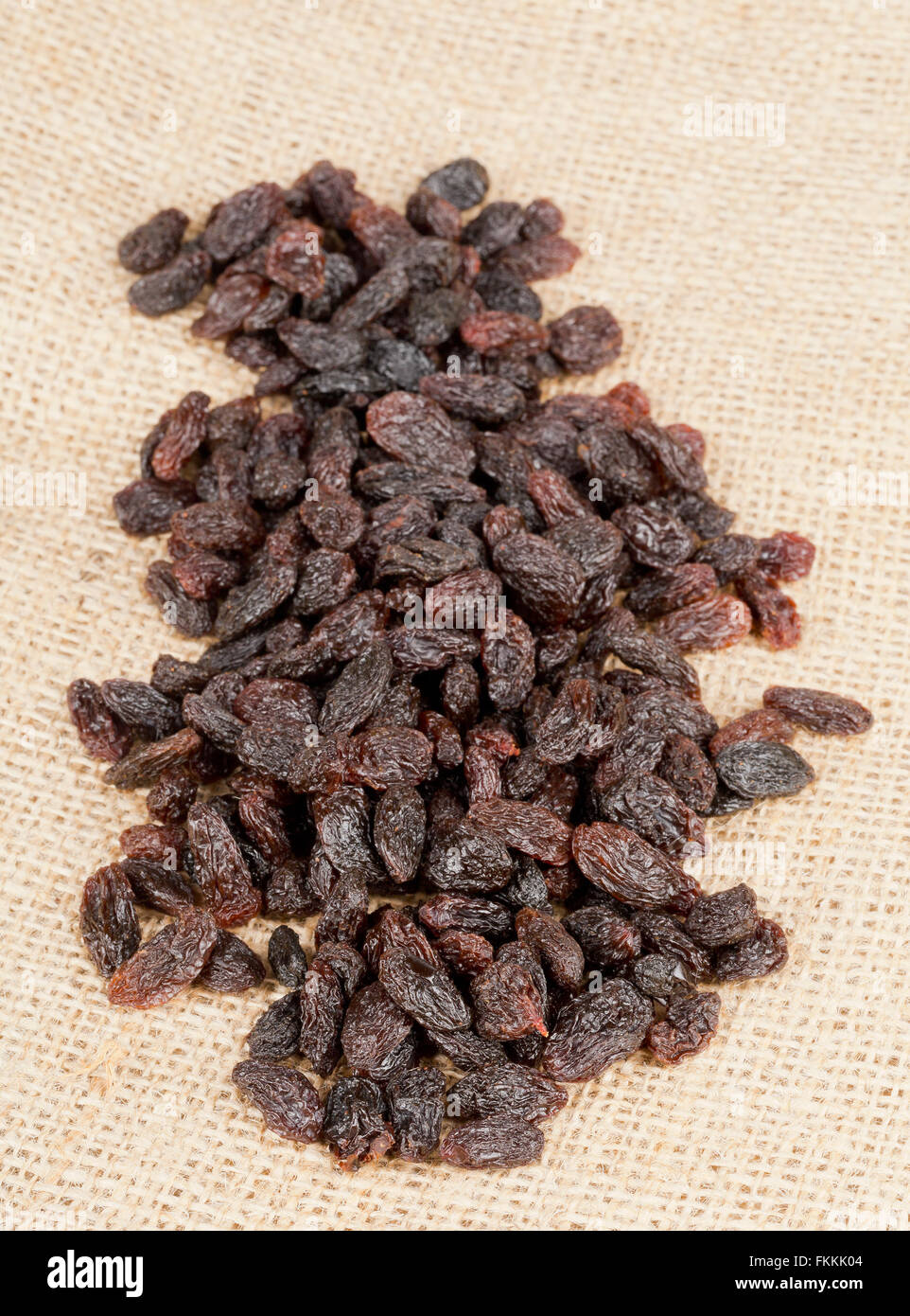 Heap of raisins close up on brown burlap sack - Stock Image