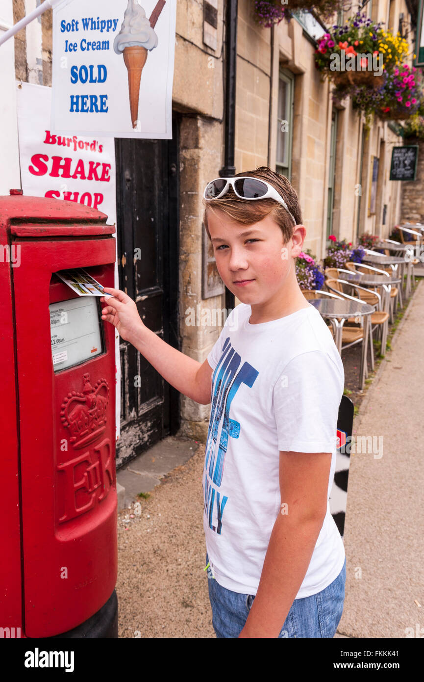 An 11 year old boy posts a postcard from his family holiday in the Uk - Stock Image