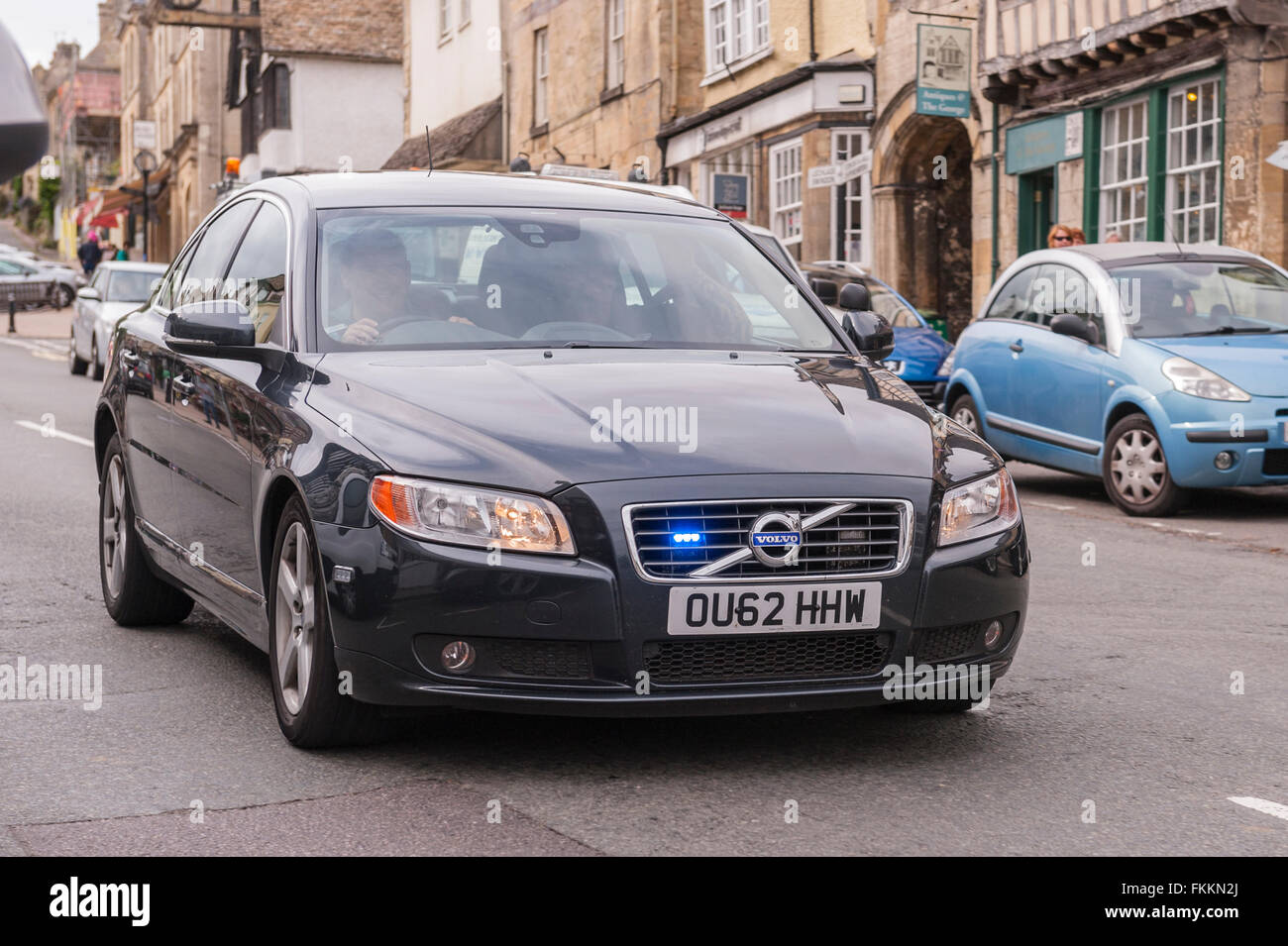 An unmarked police car flashes its blue lights as it speeds through Burford , Oxfordshire , England , Britain , Stock Photo