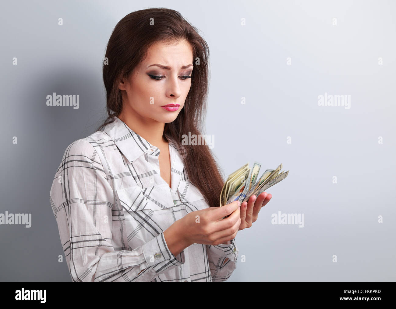 Young serious woman looking and counting dollars and thinking how little money she have earned and how she will - Stock Image