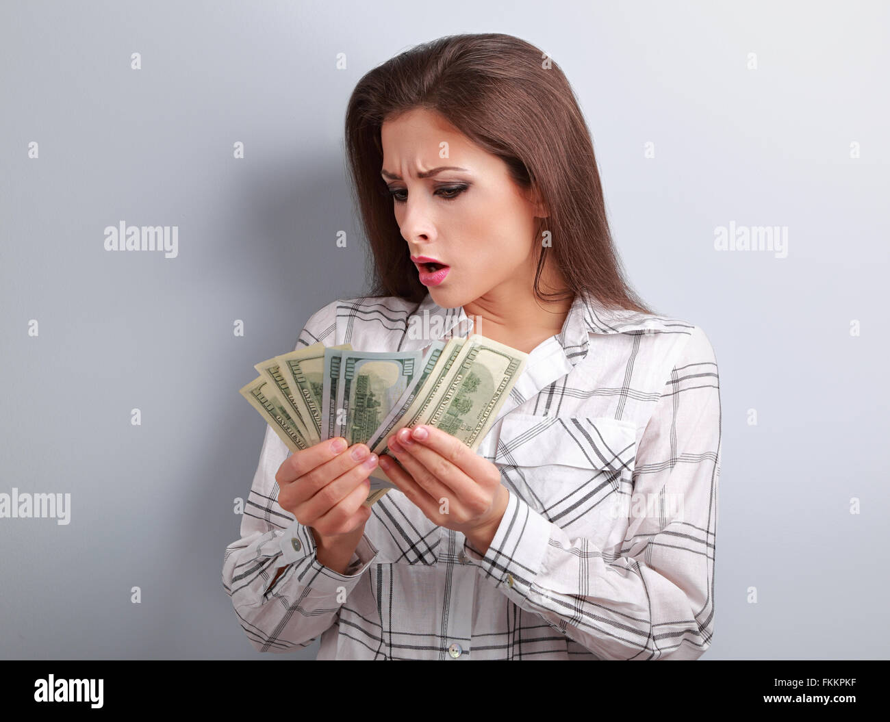 Young surprising woman looking and counting her salary and thinking how little money she have earned and how she - Stock Image
