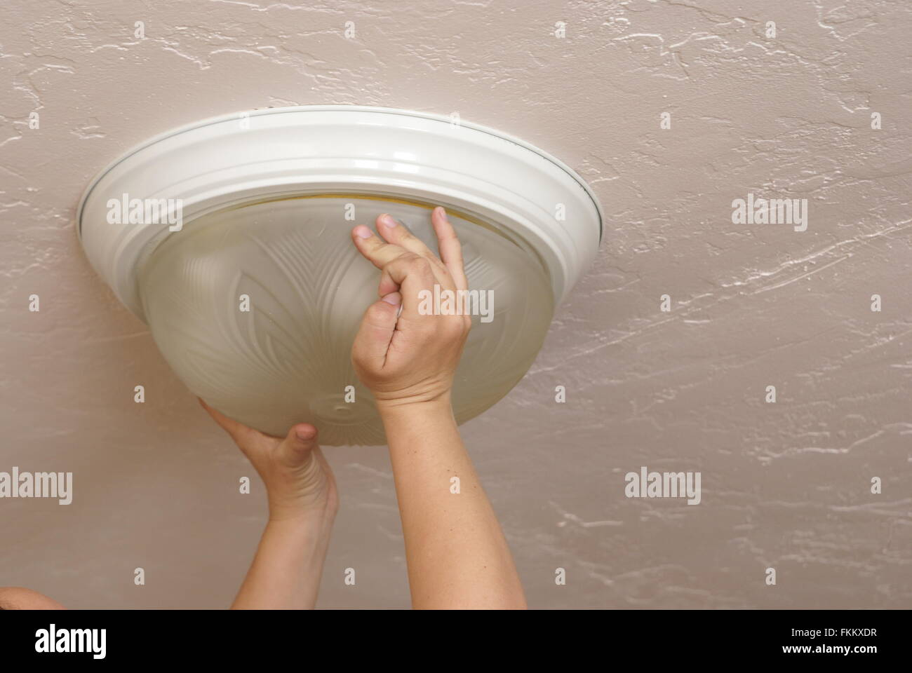 Replacing a household ceiling light globe. Home, house and everyday common activities. - Stock Image