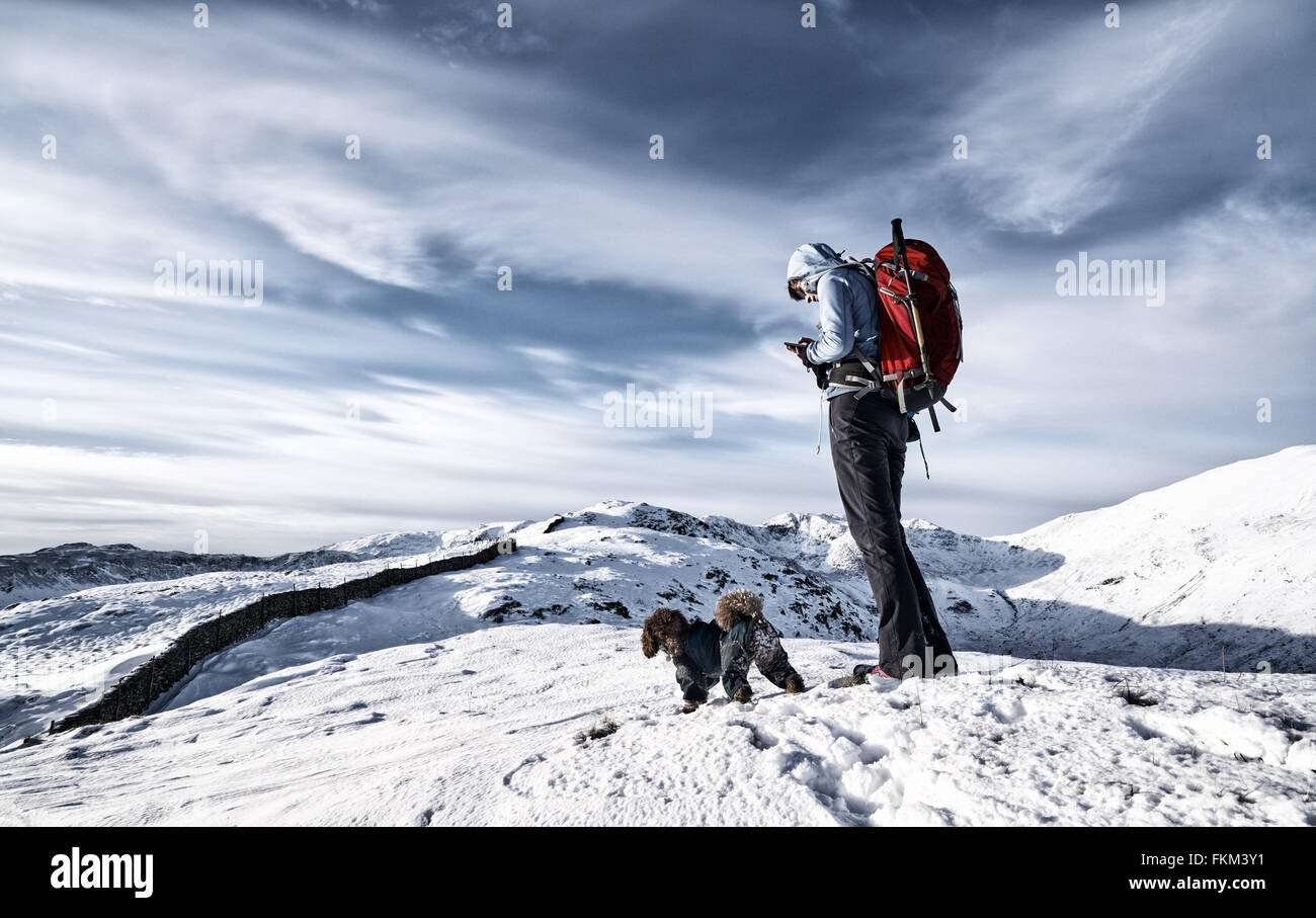 A hiker checking their position in the mountains on a GPS and map. Added  film grain and colour styling. - Stock Image