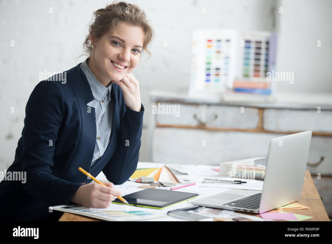 Portrait of beautiful cheerful young designer woman working at home office desk. Attractive model wearing suit holding - Stock Image