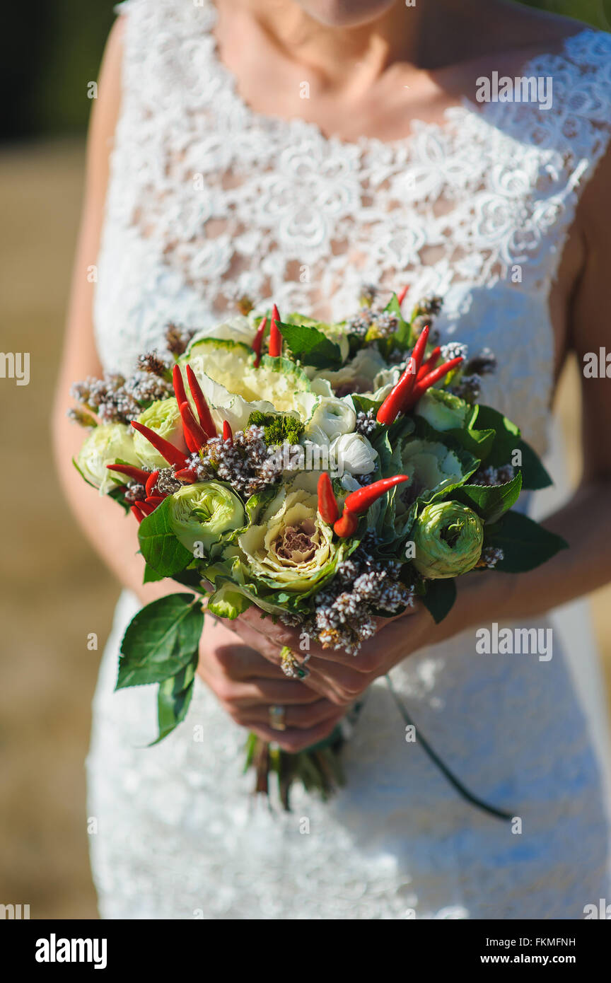 Bride in a dress holding luxurious and unusual bouquet of flowers and pepper. Outdoors. The average plan. - Stock Image