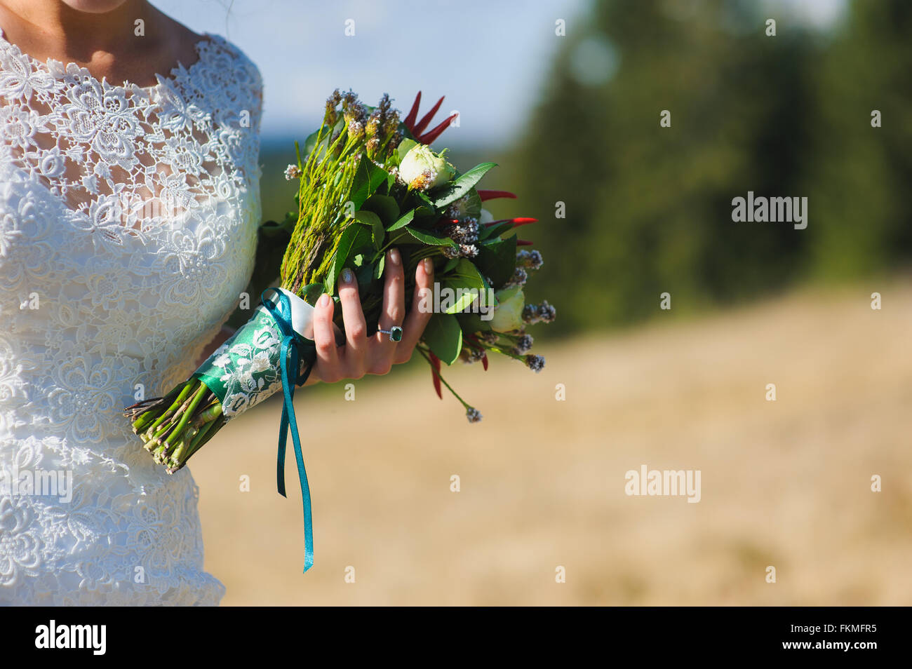Bride in a dress holding luxurious and unusual bouquet of flowers and pepper. Original unusual bouquet of flowers - Stock Image