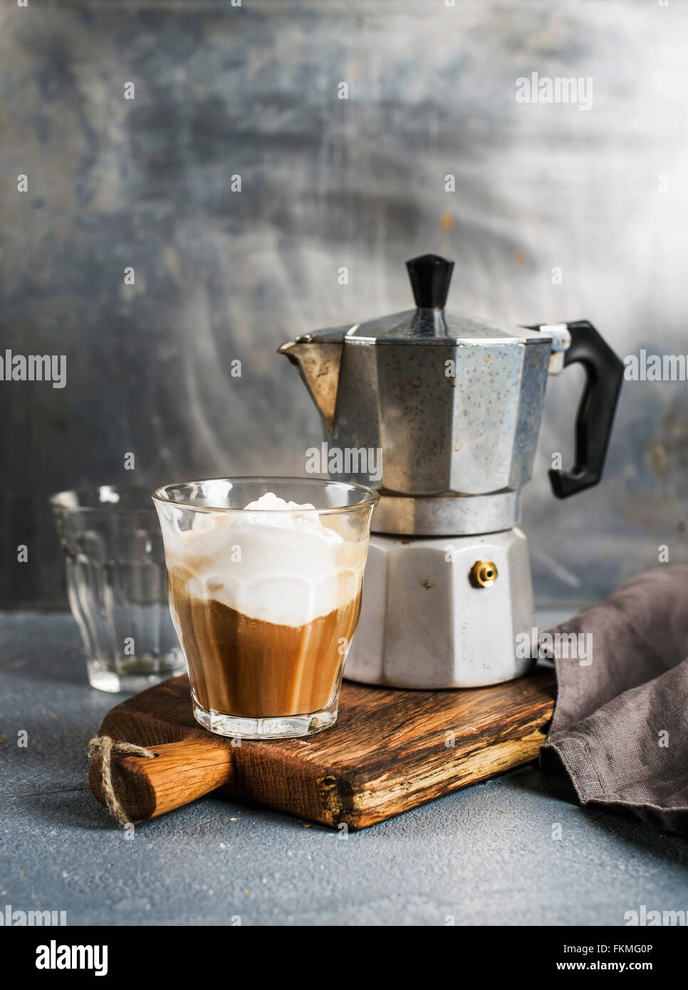 A glass of coffee with ice cream and steel moka pot on on rustic wooden board. Grey beckground, selective focus - Stock Image