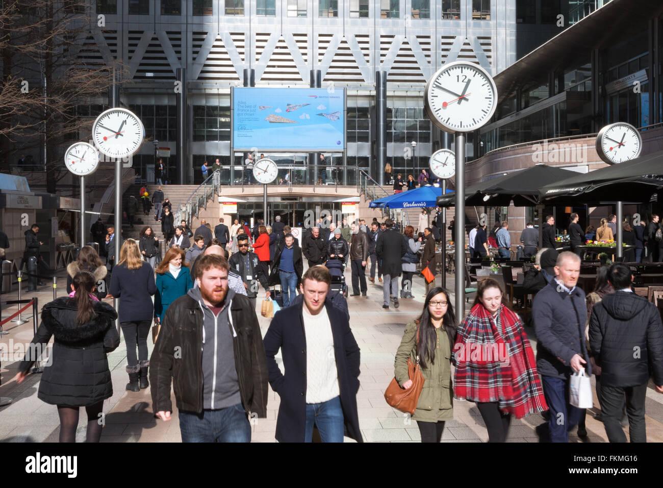 People walking through the clocks, Canary Wharf London UK - Stock Image