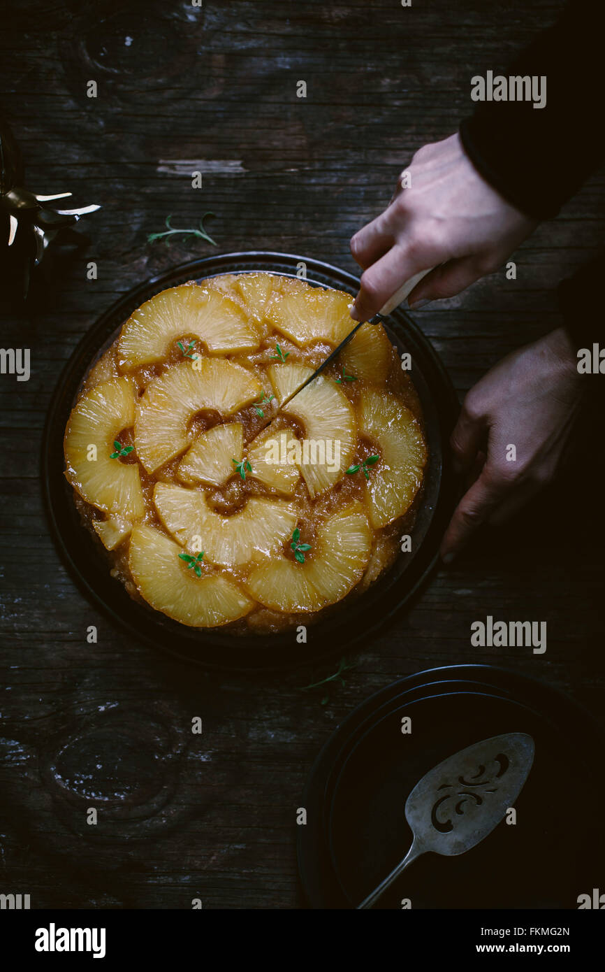 A woman is slicing an upside-down pineapple cake is photographed from the top. - Stock Image