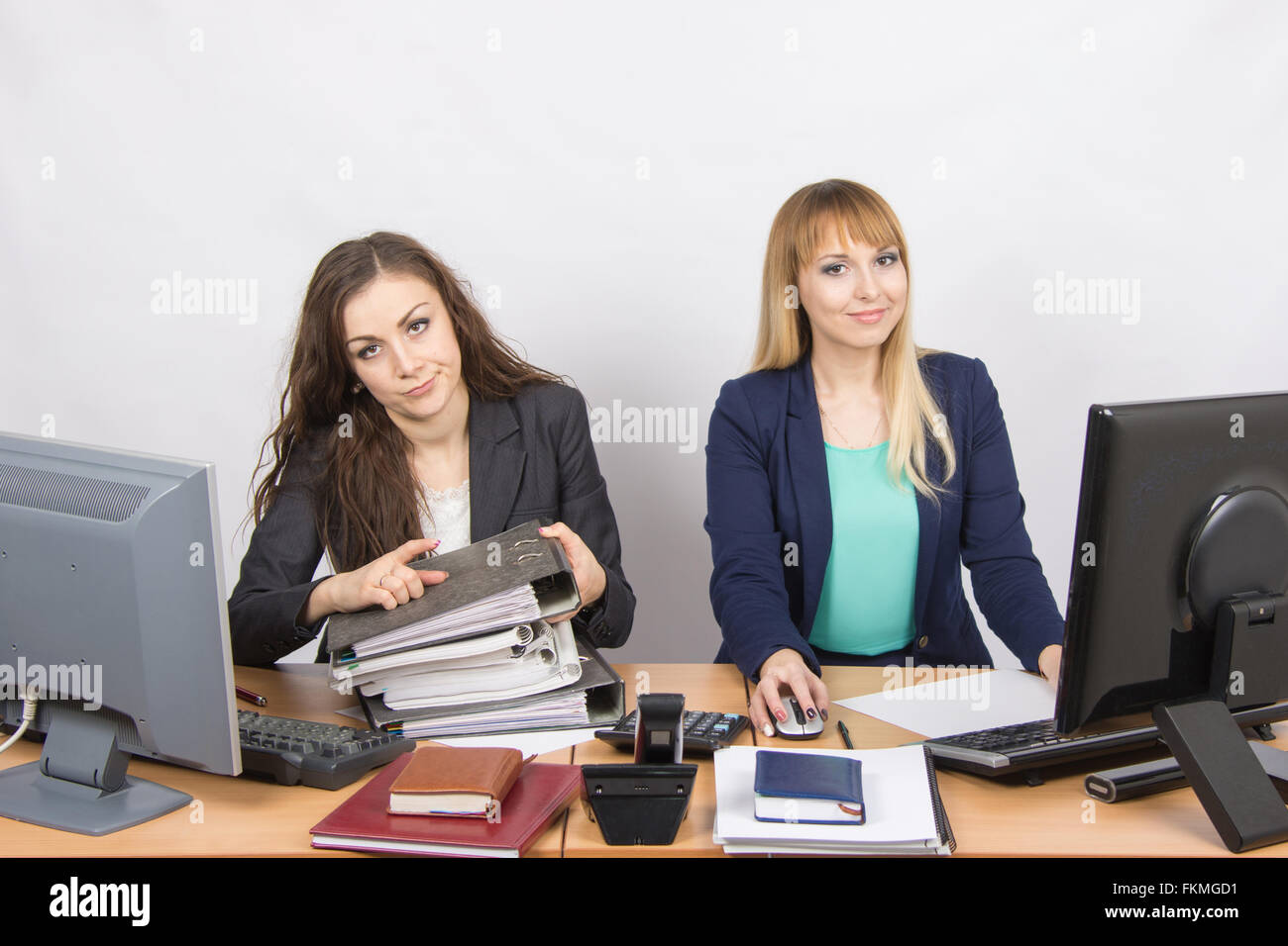 Female colleagues in the office, one littered with paper documents, the second sitting with a blank sheet of paper - Stock Image
