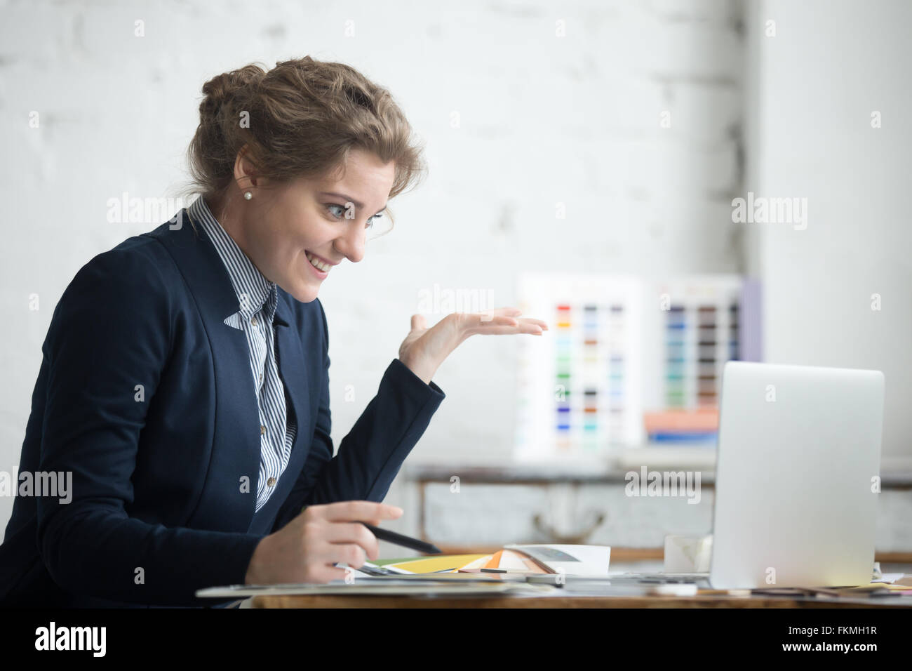 Portrait of young smiling shocked business woman wearing suit sitting at home office desk using laptop, looking - Stock Image