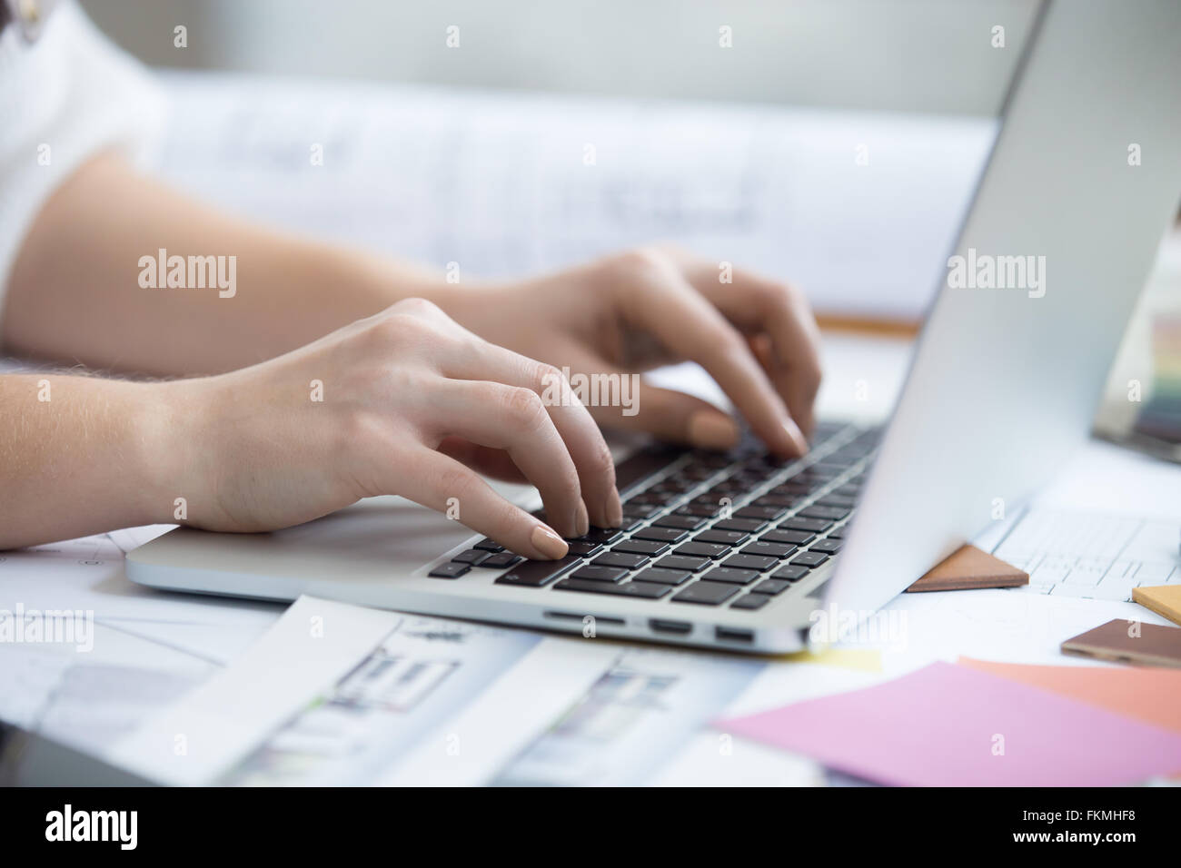 Arms of beautiful young designer woman typing on laptop sitting at home office desk covered in drawings and blueprints - Stock Image