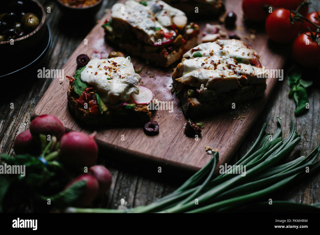 A sliced open-face chicken caprese sandwich is photographed from the front view. - Stock Image