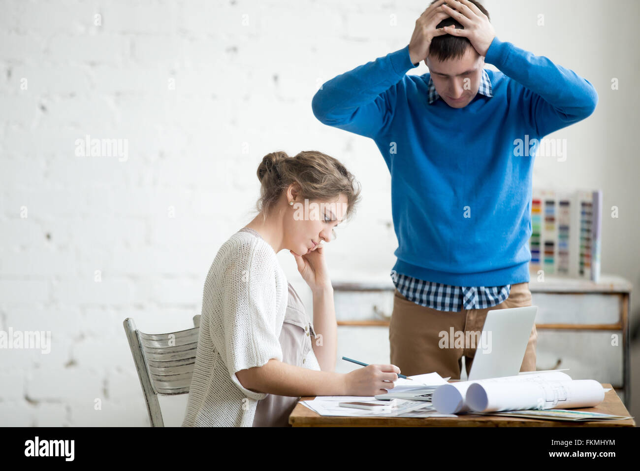 Portrait of two coworkers arguing at work, having fight at modern office. Young stressed man holding his head in Stock Photo