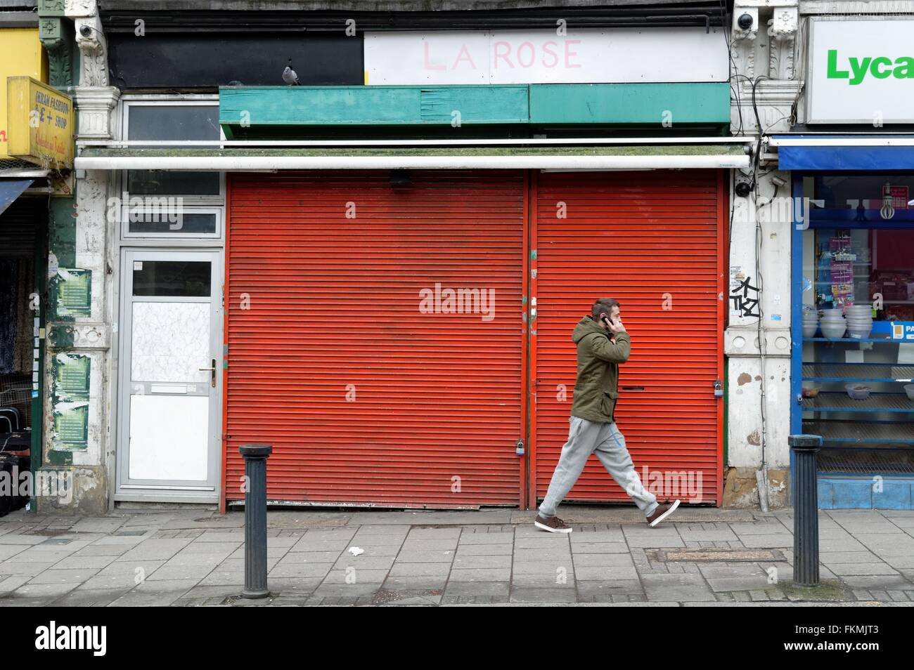 Man on phone walking by a closed shop in Harlesden London UK - Stock Image